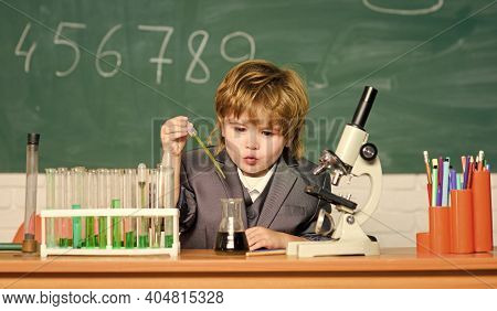 Technology And Science Concept. Boy Near Microscope And Test Tubes In School Classroom. Kid Study Bi