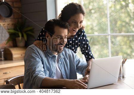Amazed Couple Shocked By Unexpected News On Laptop