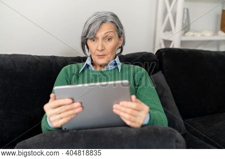 A Surprised Senior Mature Woman Sitting On The Couch, Holding A Pad And Reading News Online, Looking