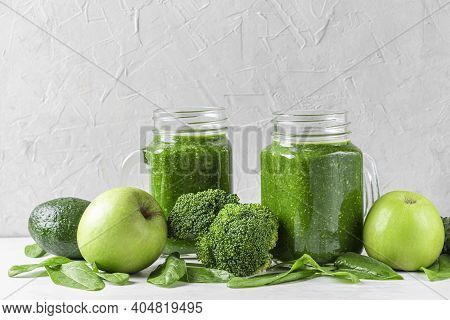 Green Healthy Detox Smoothie With Fresh Vegetables And Fruits In Jars On White Background. Healthy D