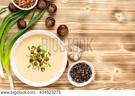 Delicious Chestnut Soup With Croutons And Herbs On A Wooden Table. Top View. Copy Space.