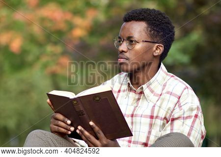 Portrait Of A Handsome Intelligent Smart Black African Afro American Young Man Sitting In A Park And