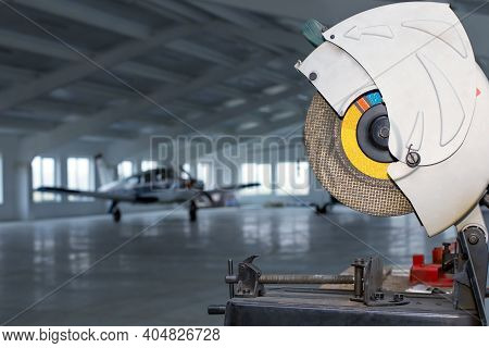 Circular Saw In Front Of Small Single Prop Engine Aircraft Plane Parked Inside Workshop Hangar With