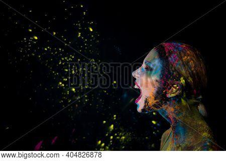Portrait Of Screaming Model With Holi Colorful Powder Art Make On Black Studio Background.