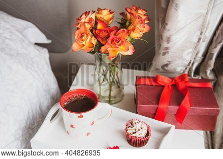 Tray With Hot Tea, Cupcake, Gift Box And A Bouquet Of Roses Flowers In Vase On The Bedside Table Aga