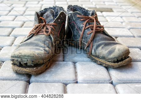 A Pair Of Dirty Boots. Old Worn Dark Blue Leather Shoes With Variegated Brown Laces. Background From