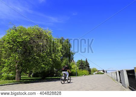 A Man Rides A Bicycle Along The Embankment By The River, Summer Street, Boulevard With Large Green T