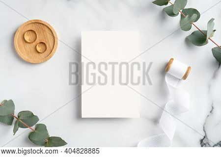 Wedding Invitation Card And Greenery On Marble Table. Elegant Bridal Flat Lay Composition With Weddi