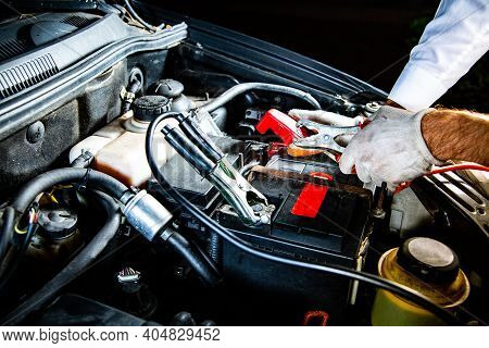 Attaching Clips To A Car Battery Under A Hood, At Night. Jump Starting A Car.