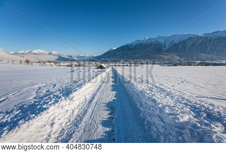 Snow Covered Walking Path Through Sunny Alpine Winter Landscape To The Village Of Wildermieming, Tir