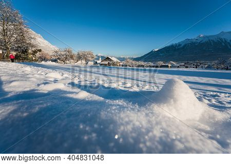 Idyllic Sunny Winter Landscape In Small Village With Sparkling Blurred Snow Piles In Austrian Alps,