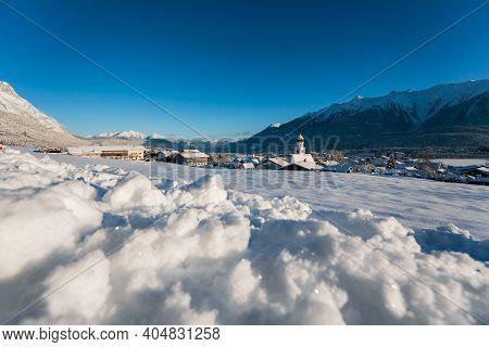 Idyllic Sunny Winter Landscape In Austrian Village With Small Avalanche In Alpine Mountains, Wilderm