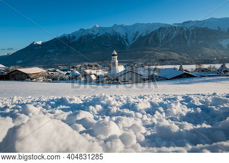 Idyllic Sunny Winter Landscape With Snow Covered Village Church With Onion Tower In Austrian Alps, W