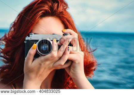 Red Haired Woman Travel Photographer, Taking Pictures On The Background Of The Sea. Rare Photographi