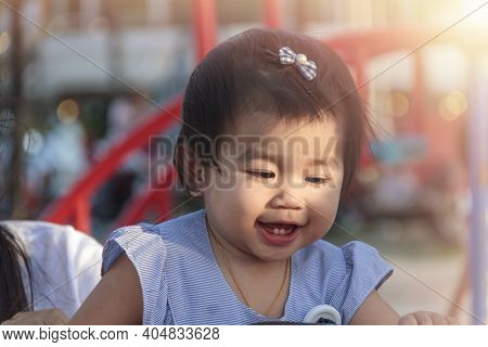 Portrait Of Smiling Happy Little Girl Enjoy With Playground Outdoor. Child Playing On Outdoor Playgr