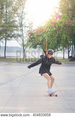 Asian Women On Skates Board Outdoors On Beautiful Summer Day. Happy Young Women Play Surfskate At Pa