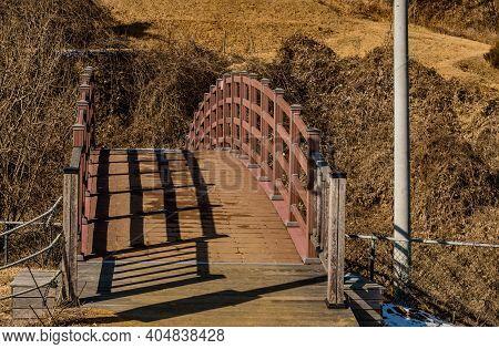 Wooden Footbridge Over Ravine In Wilderness Park On Winter Day.
