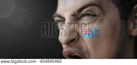 A Screaming Man With The Image Of The Fiji National Flag On His Face