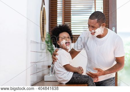 African American Man And Little Boy Having Fun Laughing With Shaving Foam On Their Faces In Bathroom