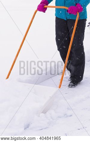 Woman Cleaning Snow With Shovel In Winter Day. Woman Shovelling Snow Walkway In Front Of House