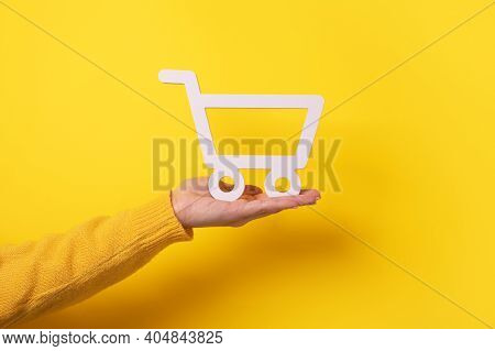 Trolley On Hand Over Yellow Background, Buying Online Concept