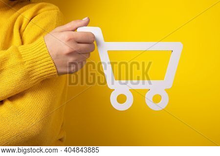 Shopping Trolley Symbol In Hand Over Yellow Background