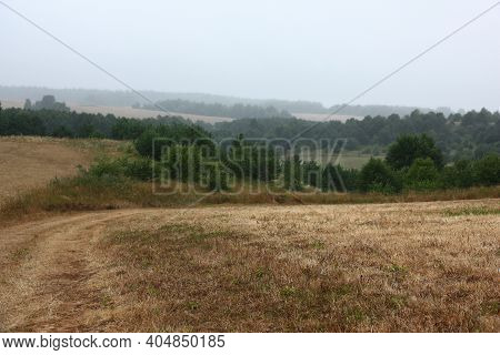Foggy Summer Morning. Hilly Area. In The Foreground The Cleaned Fields Are Visible. On A Distance Sh