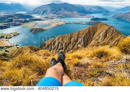 Adventure and hiking wanderlust travel vacation concept with hikers hiking boots close up. Hiker man looking at view from famous hike to Roys Peak on South Island, New Zealand. Resting and relaxing.