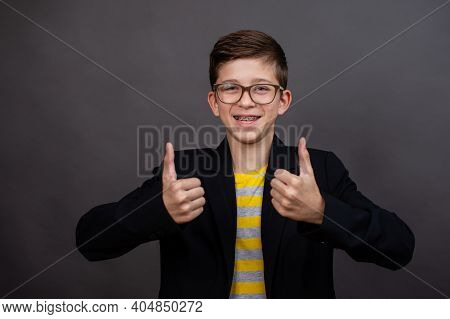 Happy Funny Boy With Glasses Show A Thumbs Up And Good Luck. On A Black, Dark Gray Background.