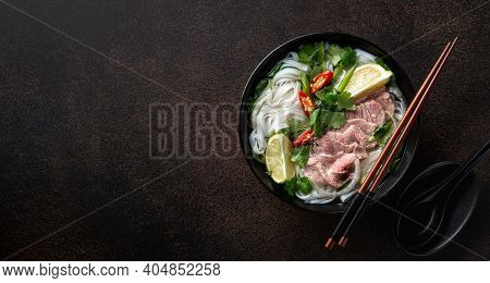 Pho Bo Vietnamese Soup With Beef And Rice Noodles On A Dark Background, Top View, Copy Space
