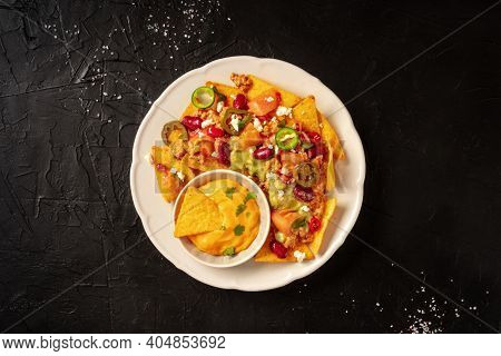Mexican Nachos With Chili Con Carne, Guacamole And Cheese Sauce, Overhead Shot On A Black Background
