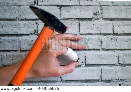 Hand With Bandaged Finger Drives Nail Into The Wall, Instead Of Nail It Hits Finger With Hammer. Man