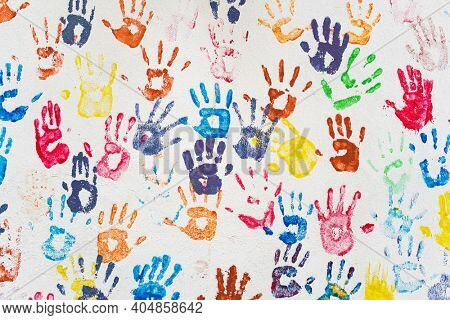 White wall with colorful multicolored hand prints. Friendship concept background. Children hand prints on the wall