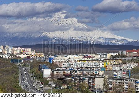 Petropavlovsk-kamchatsky. Urban Landscape With Buildings And Streets On The Background Of The Volcan