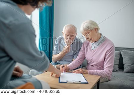 Senior Couple Having An Appointment With Health Insurance Agent And Signing The Contract