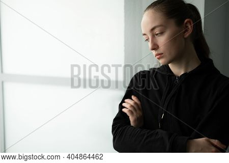 Young Beautiful Woman Looking Through A Window. Lonely Woman Feeling Depressed And Stressed In Depre