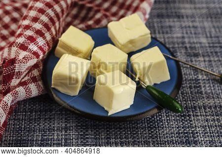 Processed Cheese Sliced Into Portions In A Blue Saucer. Soft Cheeses, Dairy Products. Selective Focu