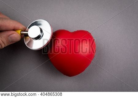 Heartbeat And Health Check. Red Rubber Heart And Stethoscope On A Gray Background