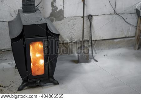 The Burning Wood-burning Stove In The Garage.