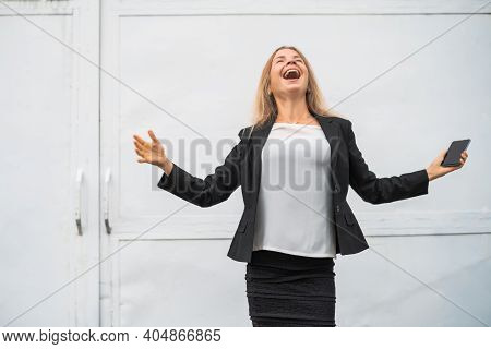 Outdoor Portrait Of Ecstatic Businesswoman Who Is Holding Smartphone.