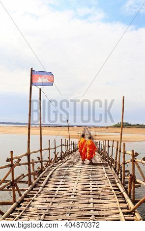 Two buddhist monks on bamboo bridge across Mekong river between Kampong Cham city and island of Koh Paen, Cambodia