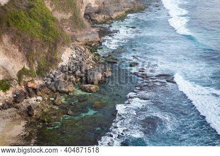 View Of Uluwatu Cliff With Pavilion And Blue Sea In Bali, Indonesia. Rocky Cliff And Sea Waves, Top
