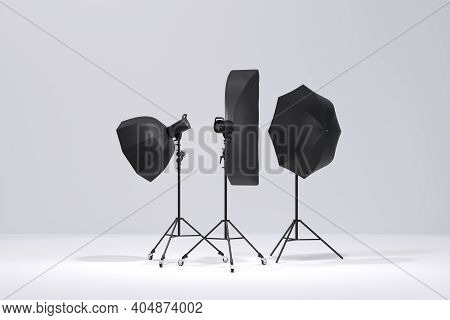 Photo Studio Lighting Stands With Flash, Umbrella And Softbox On The White
