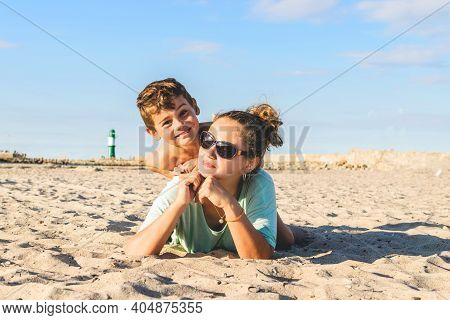 Happy Beautiful Family Beach Vacation. Mother And Child Play In The Sand In Sunny Weather By The Sea