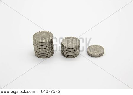 Ukrainian Money On A Light Background. Three Stacks Of Ukrainian Coins Nominal Is 5, 2 And 1 Hryvnia