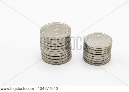 Ukrainian Money On A Light Background. Two Stacks Of Ukrainian Coins Nominal Is 5 And 2  Hryvnia