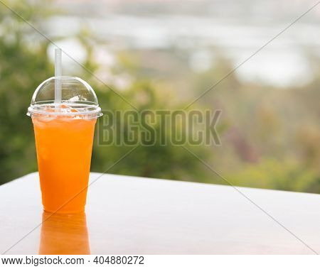 Glass of orange juice on the table of outdoor cafe