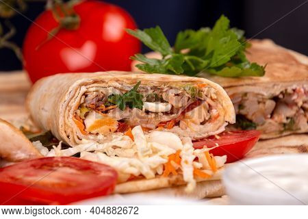 Popular Arabic Turkish Fastfood Doner Shawarma Roll With Meat And Vegetables On Dark Background