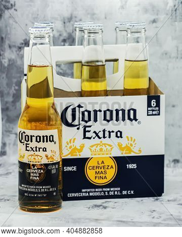 Six Bottles Of Light Beer Corona Extra In Branded Box. Produced By Cerveceria Modelo On Gray Backgro
