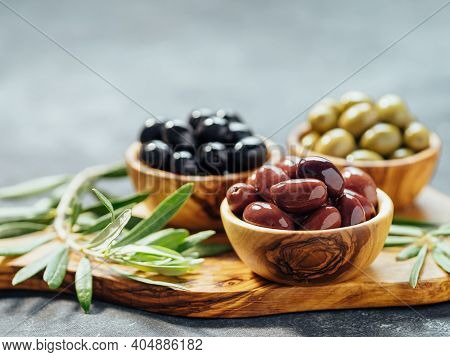 Set Of Green, Red And Black Olives On Gray Background. Different Types Of Olives In Olive Wooden Bow